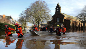 Rescue workers evacuate local residents by boat from a flooded residential street in Carlisle, Britain